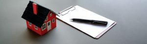Small house model with note paper and pen in grey background